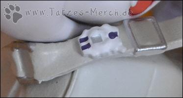 Ein kleines stilisiertes Digivice ist am Tragegurt der Tasche angebracht